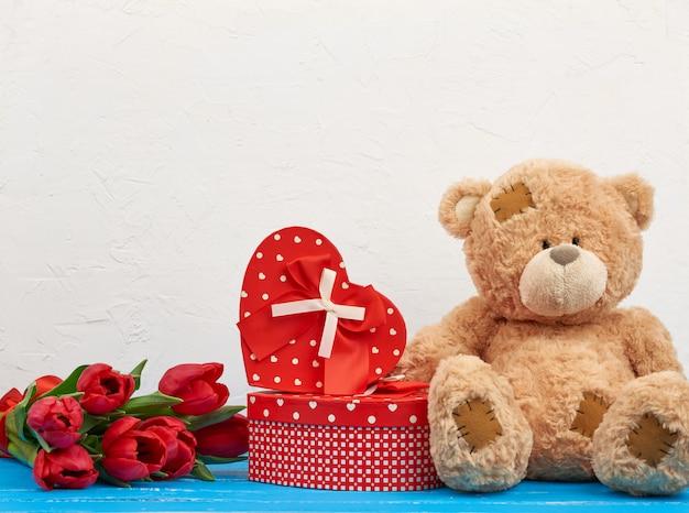 Netter brauner teddybär sitzt auf einem blauen holztisch, strauß roter tulpen, rote schachtel zum valentinstag