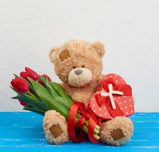 Netter brauner teddybär sitzt auf einem blauen holztisch, strauß roter tulpen, rote schachtel