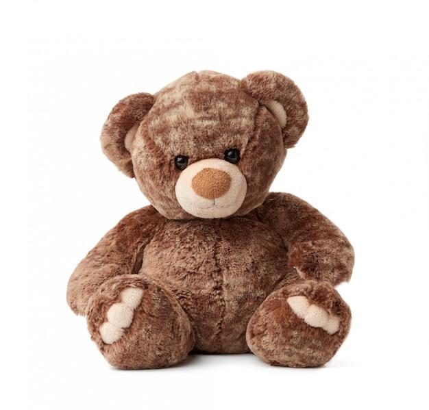 Netter brauner teddybär sitzt auf einem weißen isolierten hintergrund