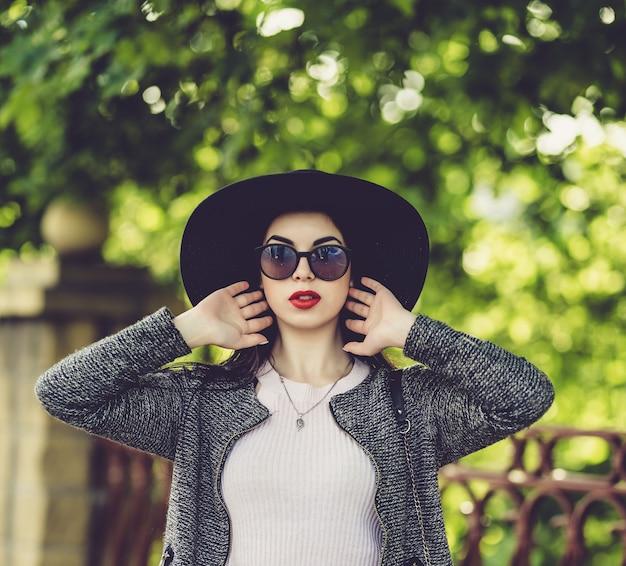 Netter brunette mit den roten lippen im hut und in sonnenbrille, die in der stadt aufwerfen