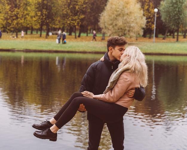 Netter brunettekerl hält in seinen armen und küsst ein schönes blondes mädchen. liebende teenager sind glücklich