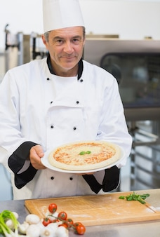 Netter chef, der pizza darstellt