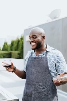 Netter chef mit grillzangen und einem weinglas