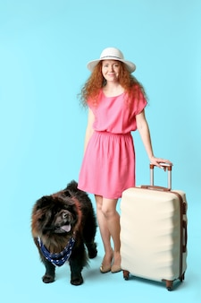Netter chow-chow-hund und junge frau mit koffer auf farboberfläche