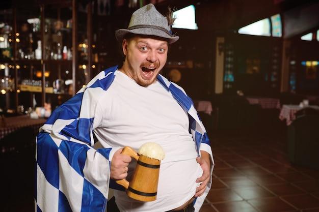 Netter dicker mann mit einem dicken bauch mit einer oktoberfestflagge und einem bayerischen hut