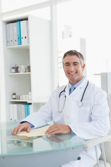 Netter doktor, der an seinem schreibtisch sitzt