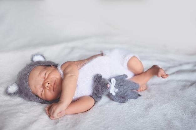 Netter emotionaler neugeborener kleiner junge, der im kinderbett in einem strickanzug mit spielzeug schläft.