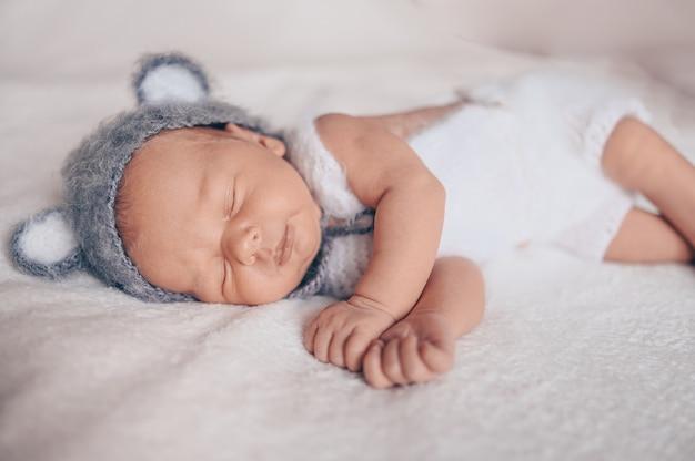 Netter emotionaler neugeborener säuglingsbaby, das im kinderbett in einem strickanzug mit ohren schläft.