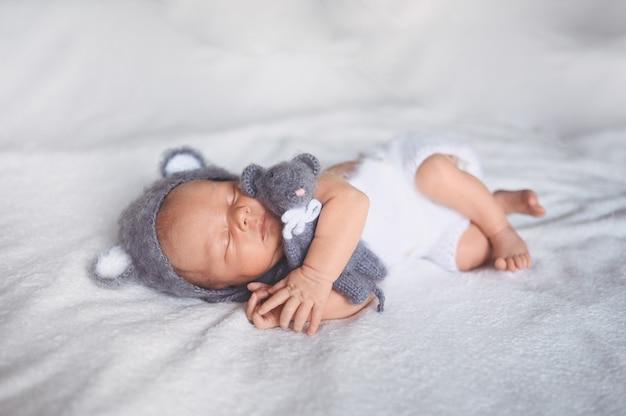 Netter emotionaler neugeborener säuglingsbaby, das im kinderbett in einem strickanzug mit spielzeug schläft.