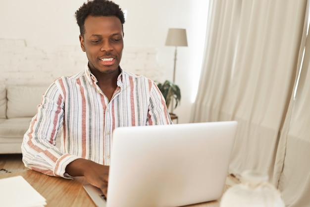 Netter entspannter junger afrikanischer mann, der unter verwendung eines generischen tragbaren computers für das chatten mit freunden sitzt, videospiele online spielt, glücklichen blick hat