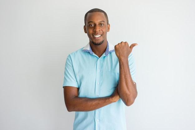Netter erfolgreicher afrikanischer mann, der beiseite zeigt und kamera betrachtet.