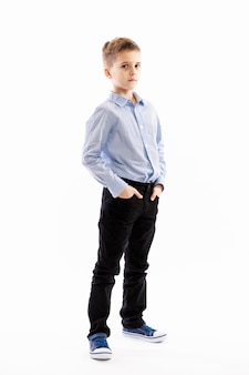 Netter ernster junge, den ein schüler steht, seine hände in seinen taschen halten