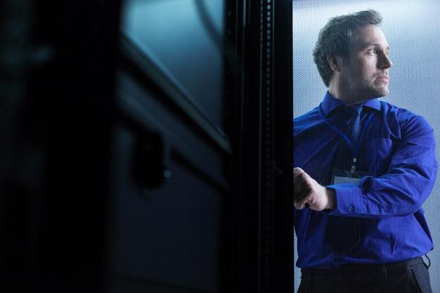 Netter ernsthafter erwachsener mann, der beiseite schaut und den schlüssel hält, während eine tür im serverraum öffnet