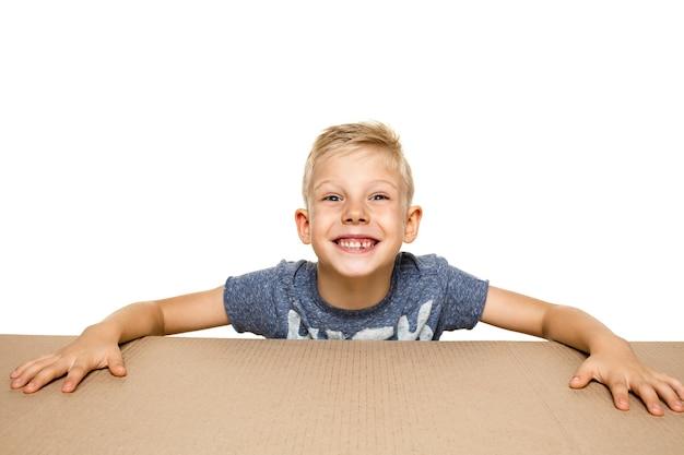Netter, erstaunter kleiner junge, der das größte paket öffnet. schockiertes, glückliches junges männliches model auf karton