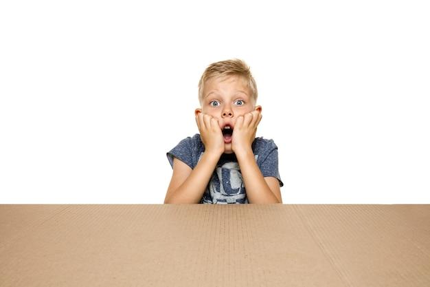 Netter, erstaunter kleiner junge, der das größte postpaket öffnet. schockiertes, glückliches junges männliches model auf karton