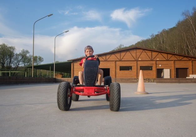 Netter europäischer junge, der ein kinderauto mit pedalen auf der rennstrecke im sommer reitet