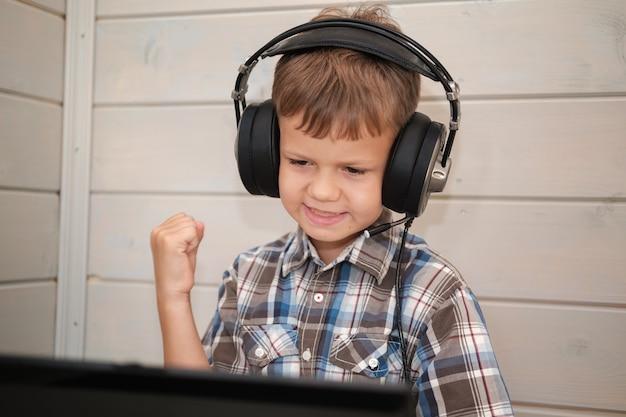 Netter europäischer junge in kopfhörern mit einem mikrofon wirft glücklich seine hände hoch sitzend auf einem laptop.