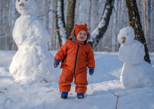 Netter europäischer junge und der lustige schneemann in den verschneiten wäldern an einem wintertag im schnee