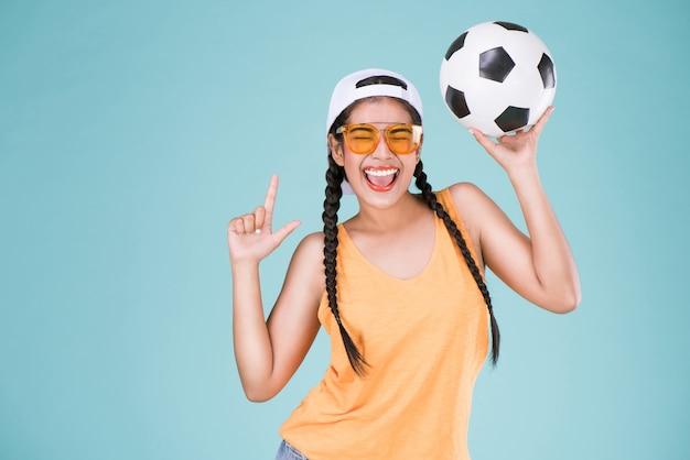 Netter frauenfan der fußballmeisterschaft. geeignetes mädchen, das ball über blauem hintergrund hält.