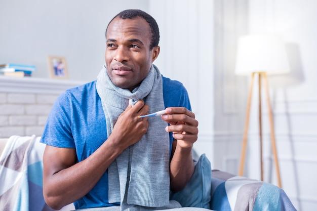 Netter freudloser kranker mann, der auf dem sofa sitzt und ein thermometer hält, während er beabsichtigt, seine körpertemperatur zu messen
