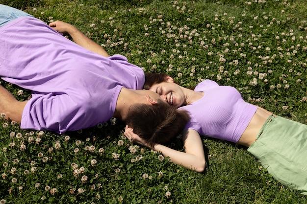 Netter freund und freundin, die auf gras liegen