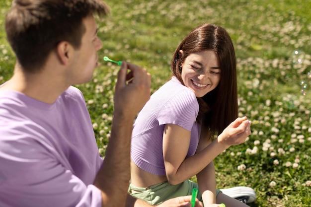 Netter freund und freundin spielen mit seifenblasen