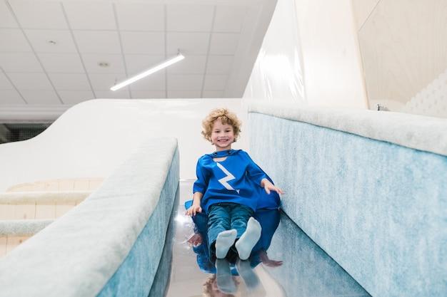 Netter fröhlicher kleiner junge im blauen kostüm des übermenschen, der rutschenrutsche auf spielplatz im modernen kinderzentrum bewegt