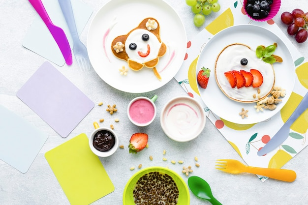 Netter frühstückshintergrund, kinderpfannkuchen und schokoladenmüsli