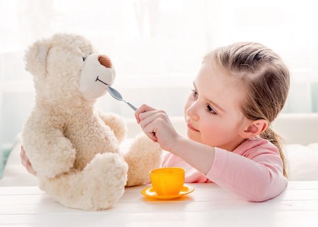 Netter fütterungsspielzeug-teddybär des kleinen mädchens