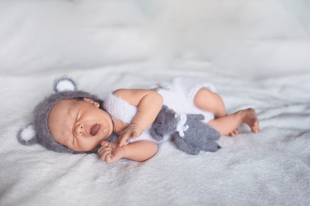 Netter gähnender neugeborener kleiner junge, der in krippe in einem strickanzug mit ohren schläft.