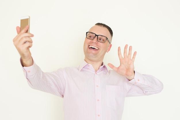Netter geschäftsmann, der videokonferenzen auf smartphone verwendet.