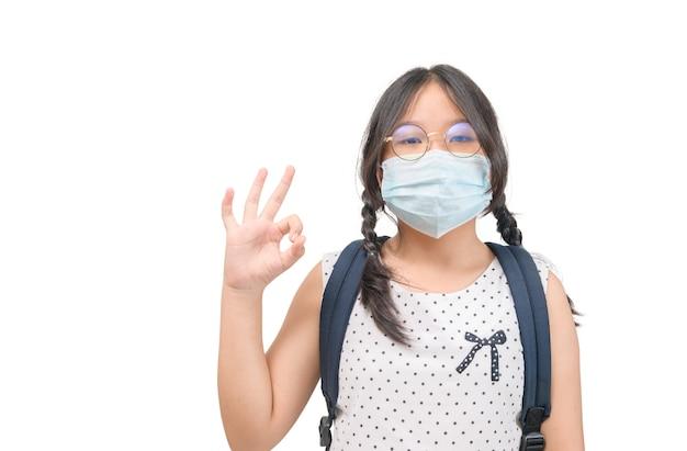 Netter glücklicher asiatischer student trägt maske und zeigt ok-zeichen einzeln auf weiß. covid-19 schützen und zurück zum schulkonzept