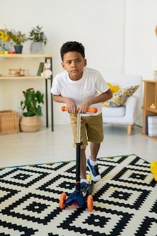 Netter glücklicher gemischter vorschulkind in der freizeitkleidung, die spielzeugplastikroller auf schwarzweiss-teppich im wohnzimmer oder im kindergarten fährt