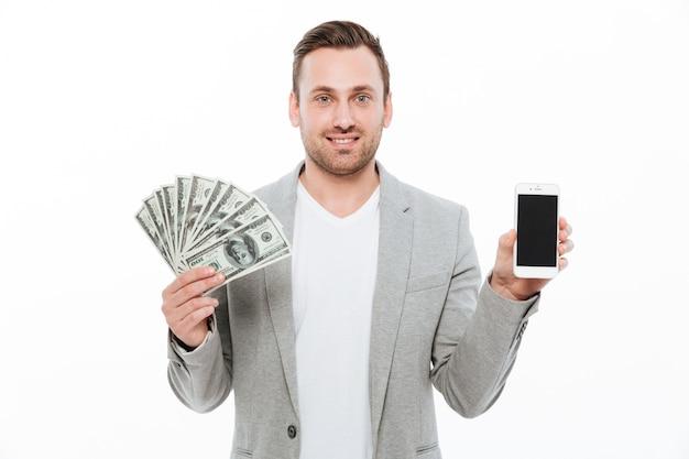 Netter glücklicher geschäftsmann, der geld hält und anzeige des telefons zeigt.