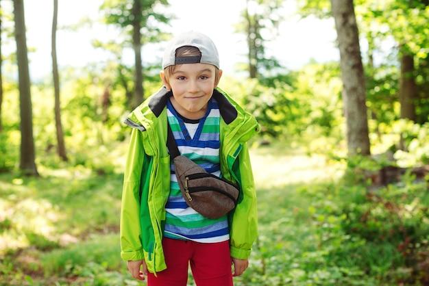 Netter glücklicher junge, der spaß im wald hat. familiencampingzeit. sommerurlaub, familienzeit in der natur.