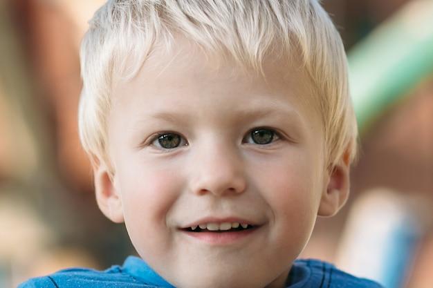 Netter glücklicher junge mit dem blonden haar, das spaß auf dem spielplatz am sonnigen sommertag hat.