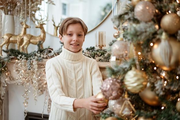 Netter glücklicher junge verzieren weihnachtsbaum zu hause
