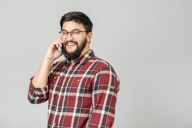 Netter glücklicher junger mann, der die lächelnde unterhaltung am telefon lacht
