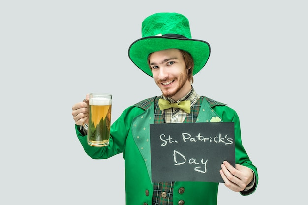 Netter glücklicher junger rothaarigemann, der becher bier und dunkle platte in den händen hält. er schaut und lächelt. es ist st. patrick's day. isoliert auf grau.