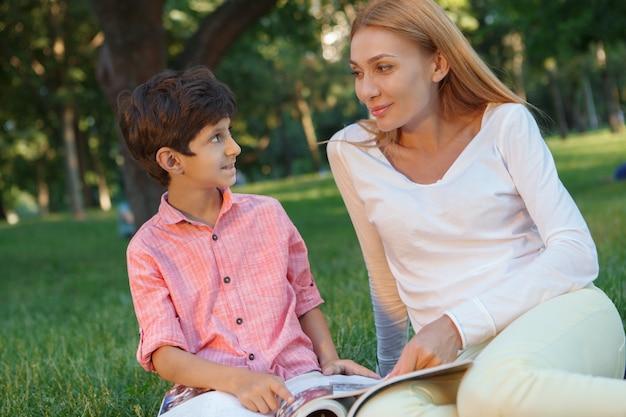 Netter glücklicher kleiner junge, der seine lehrerin anlächelt und mit einem buch im gras sitzt