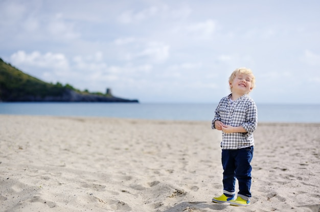 Netter glücklicher kleiner junge genießen ferien auf strand nahe tyrrhenischem meer. lustiges nettes kind, das ferien macht und sommer genießt.