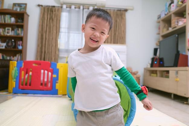 Netter glücklicher lächelnder asiatischer kleiner junge, der zu hause in der spielzeugtunnelröhre drinnen spielt und spaß hat