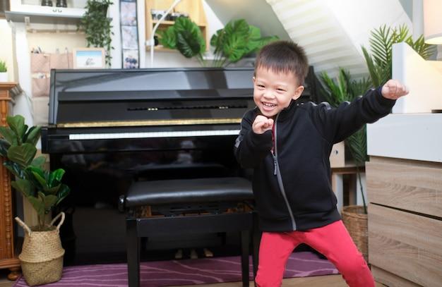 Netter glücklicher lächelnder kleiner asiatischer kinderjunge, der spaß hat, zu musik drinnen im wohnzimmer zu hause zu tanzen