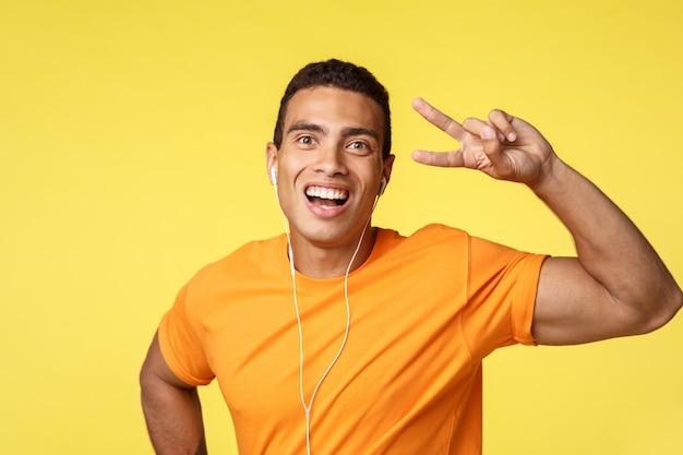 Netter, glücklicher lächelnder mann im orange t-shirt, hören motivmusik in den kopfhörern und zeigen das friedens- oder siegeszeichen und grinsen optimistisch, genießen lieblingslieder und stehen den gelben optimistischen hintergrund