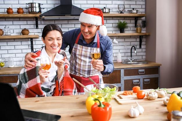 Netter glücklicher mann und frau, die weihnachten oder neues jahr feiert. zusammen im zimmer sitzen und lächeln. laptop betrachten. mann tragen hut. weingläser in händen halten.