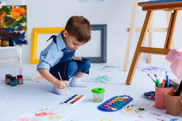 Netter, glücklicher, weißer junge im blauen hemd und in den jeans zeichnet mit farben