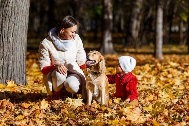 Netter, glücklicher, weißer junge im roten hemd, der mit hund zwischen gelben blättern lächelt und spielt. kleines kind hat spaß mit seiner mutter im herbstpark. konzept der freundschaft zwischen kindern und haustieren, glückliche familie