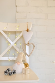 Netter gnom mit langem bart. weißer weihnachtszwerg in der nähe von herzen, tannenzapfen und warmen lichtern und ziegelmauer
