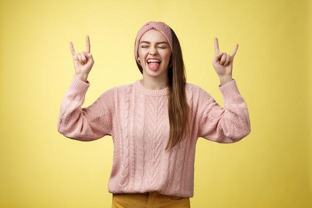 Netter heavy-metal-liebhaber, der rock-roll-symbol zeigt, das amüsiert und glücklich herumspielt, lieblingsmusik herumalbern, die aufgeregt und erfreut gegen gelben hintergrund im gestrickten outfit aufwirft