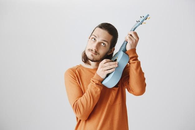 Netter hipster-typ stimmt saiten ab und spielt ukulele